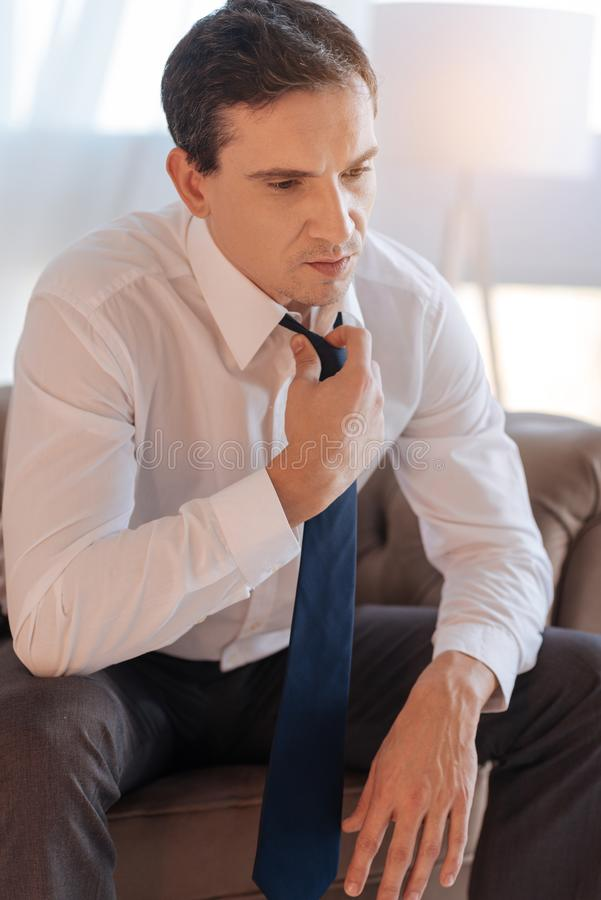 Serious young specialist looking tired while taking off his tie. Tiresome day. Thoughtful calm quiet man sitting in an armchair and looking exhausted while royalty free stock images
