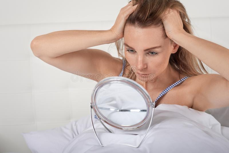 Serious young woman in bed looking at herself in a small portable hand mirror stock photography