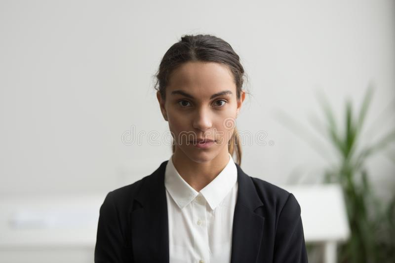 Serious young woman business leader looking at camera, headshot. Serious young woman business leader in suit looking at camera, confident strict female manager stock images
