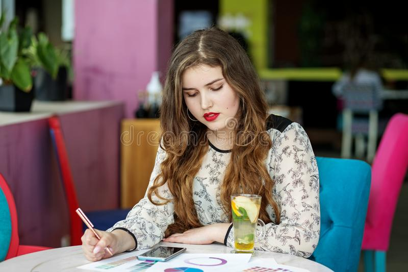 Serious young woman decides on the set plans. Citrus tea with mint. The concept of work, business, education, freelance, lifestyle.  stock images