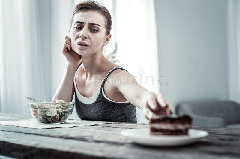 Serious young woman dreaming about tasty dessert. Low spirits. Attentive female person wrinkling forehead while having dinner stock images