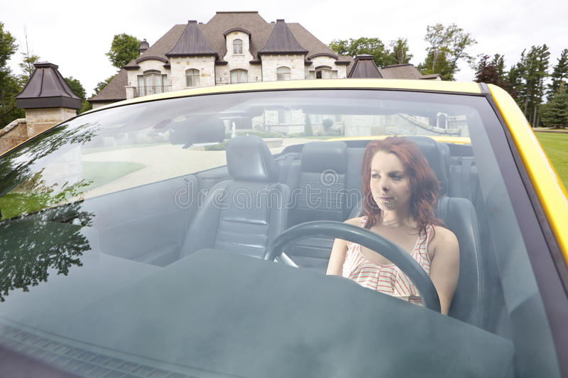 Serious young woman driving away from house stock photography