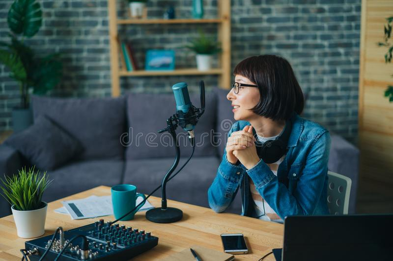 Serious woman in glasses speaking in microphone recording speech for audio blog stock photo