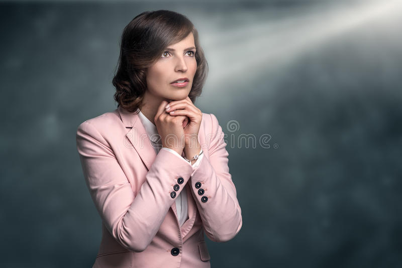 Serious young woman with hands clasped in prayer stock image