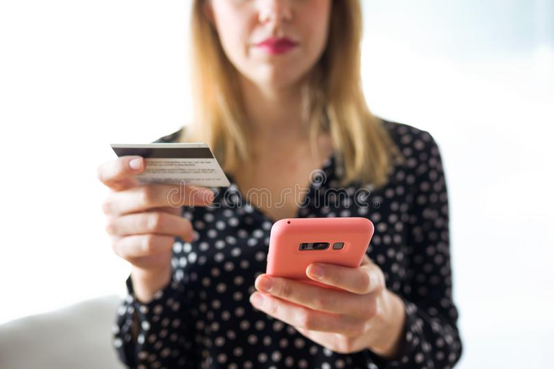 Serious young woman holding white credit card for shopping online with mobile phone in living room at home. Close-up of serious young woman holding white credit royalty free stock photos