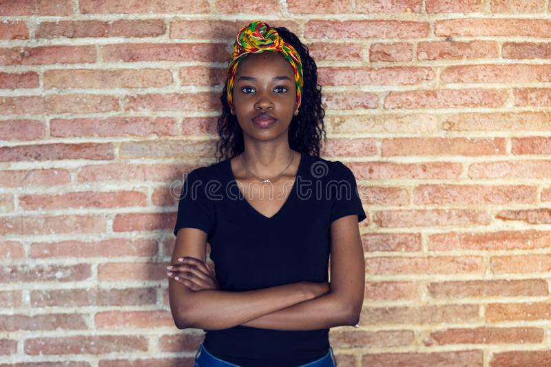 Serious young woman looking at camera with arms crossed while standing in front of a wall stock images