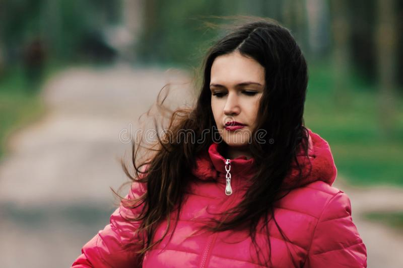 Serious young woman in red autumn jacket stock images