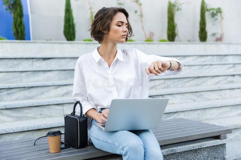 Serious young woman sitting on bench outdoors at the street, using laptop computer, royalty free stock photography