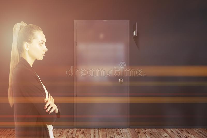 Businesswoman near a closed door in gray office stock photo