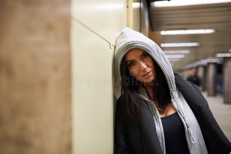 A serious young woman standing at a subway station royalty free stock images