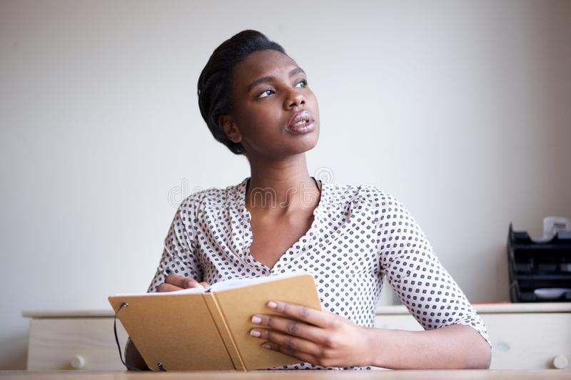 Serious young woman thinking and writing in journal royalty free stock image