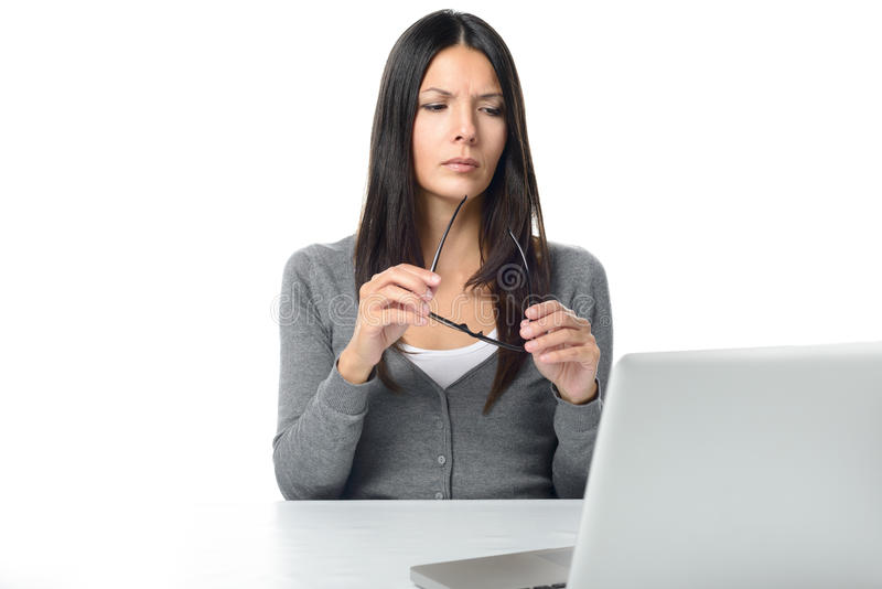 Serious Young Woman Using Laptop. Serious Long Hair Young Woman working on her Laptop with glasses in her hand, Isolated on White Background royalty free stock photo