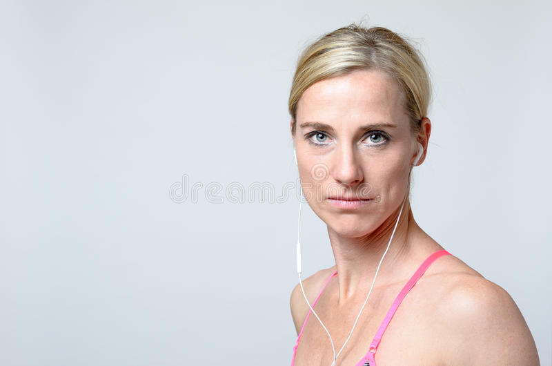 Serious young woman wearing earphones royalty free stock images