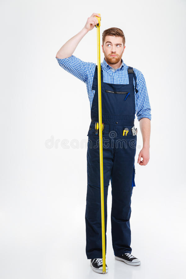 Serious young worker standing and measuring his growth with tape stock photos