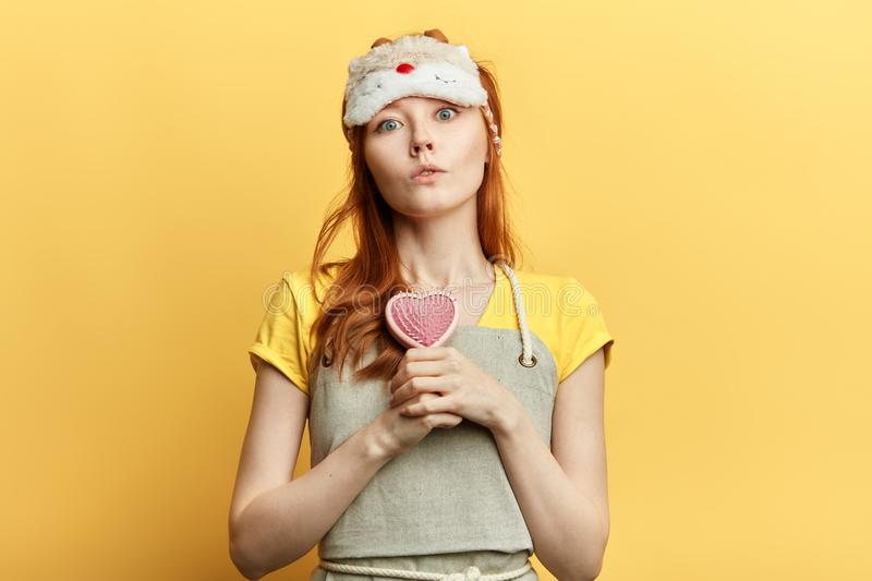 Seriousbeautiful girl holding a hairbrush stock images