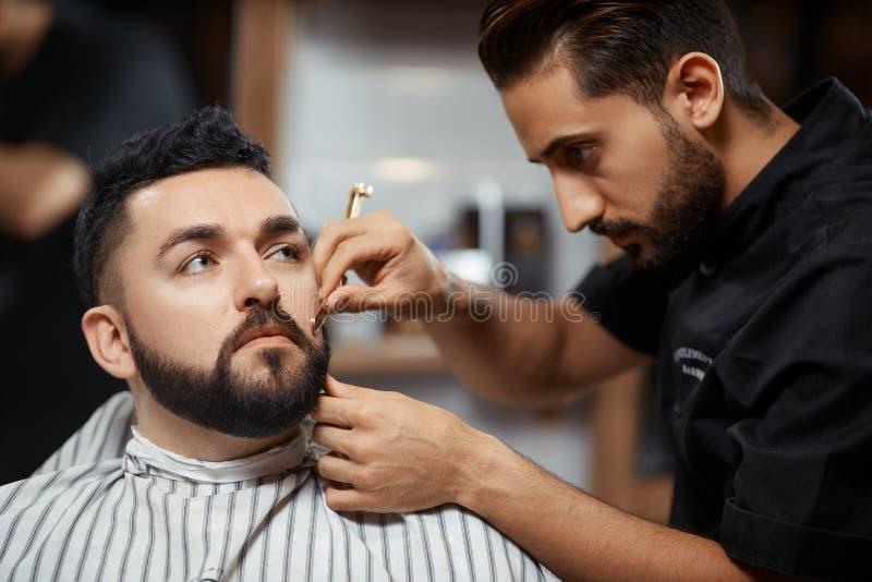 Seriousc fryzjer w fryzjera męskiego sklepu tnącym chlebie z żyletką fotografia royalty free