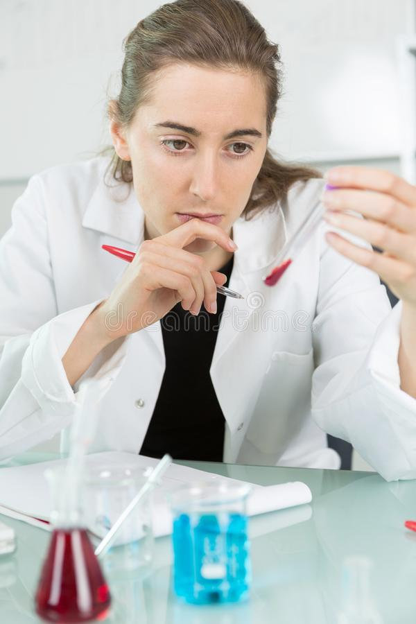 Seriously looking female doctor with blood probe and request form. Female stock images