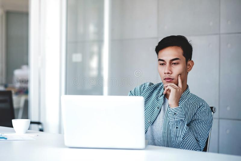 Seriously Young Businessman Working on Computer Laptop in Office. Hand on Shin, Sitting on Desk with Thoughtful Posture. royalty free stock images