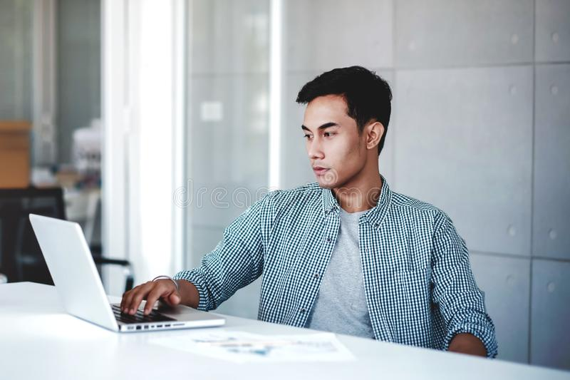 Seriously Young Businessman Working on Computer Laptop in Office. Sitting on Desk with Thoughtful Posture. Concentrated and Smart royalty free stock photos