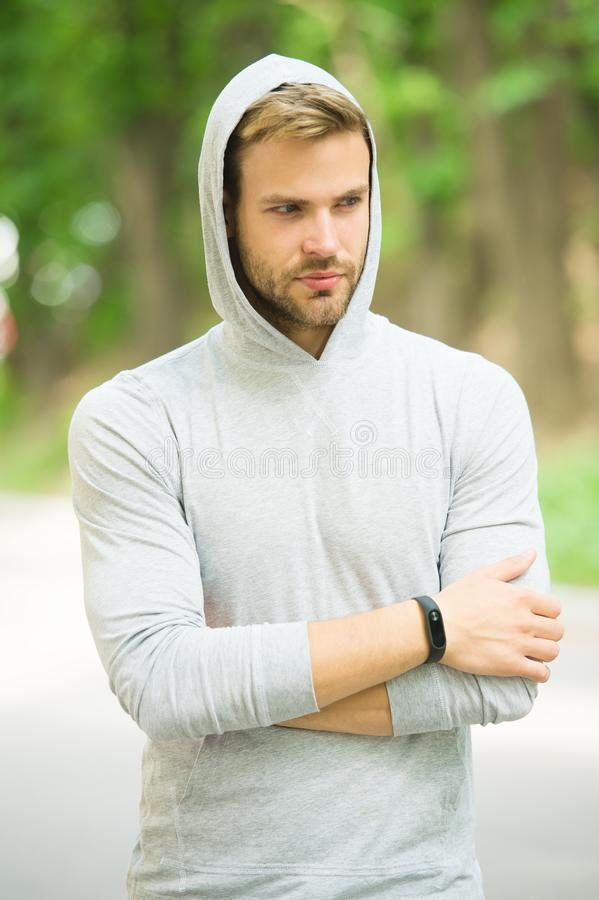 Seriousness and masculinity. sportswear fashion. sportsman relax after training outdoor. handsome unshaven man in hood stock photography