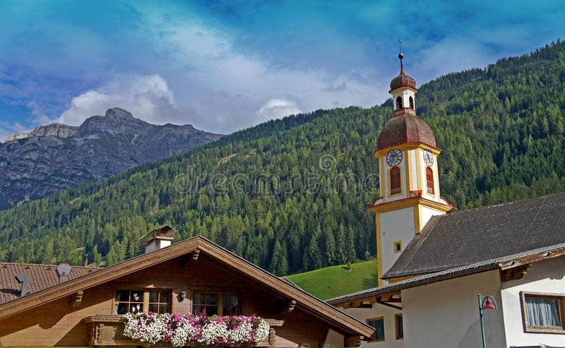 The Serles and a steeple. The Serles and the church tower of Neustift im Stubaital, Tyrol, in the foreground flowers on a balcony royalty free stock photography