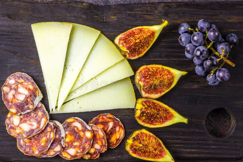Serowe figi, winogrona, chorizo nad czarnym grunge tłem fotografia stock