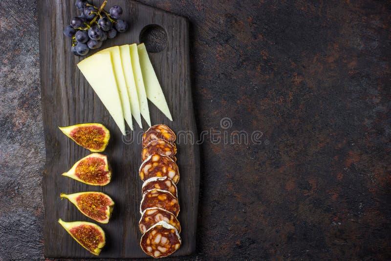 Serowe figi, winogrona, chorizo nad czarnym grunge tłem zdjęcia stock