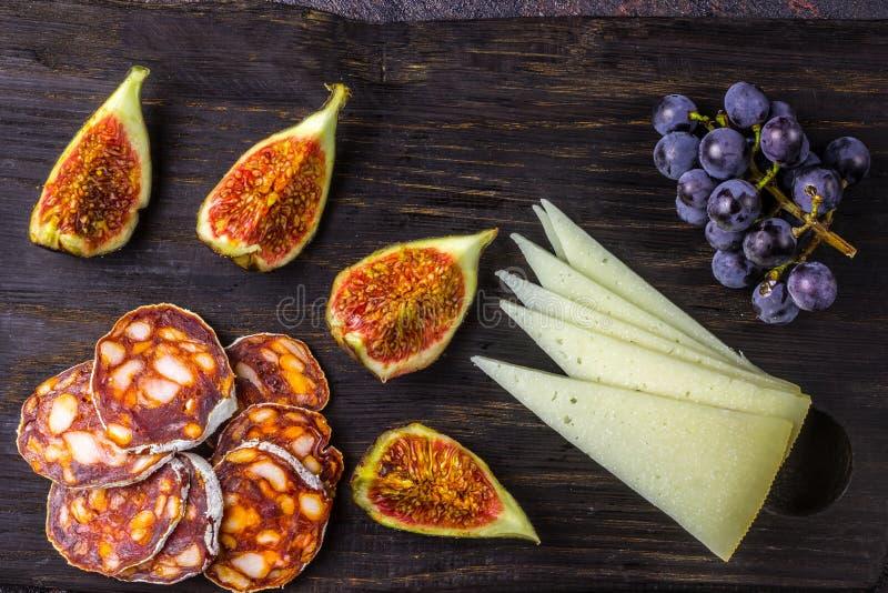 Serowe figi, winogrona, chorizo nad czarnym grunge tłem obrazy stock