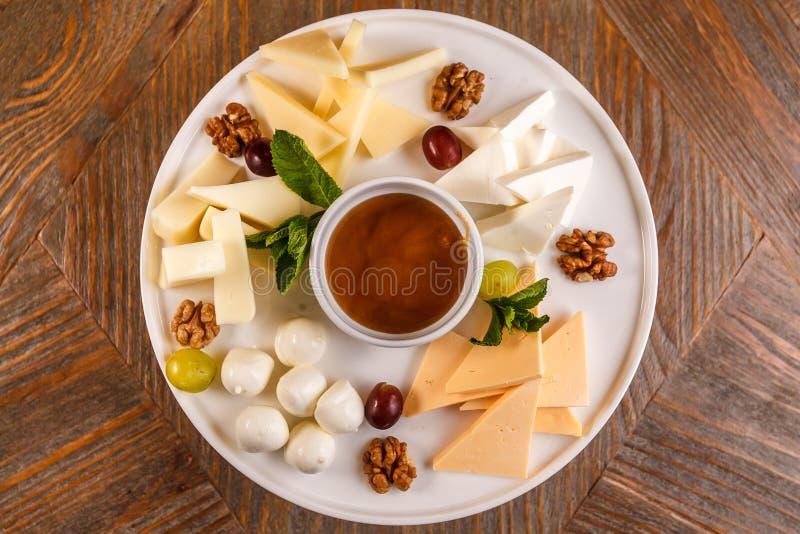 Serowego talerza asortyment różnorodni typ ser i miód na bielu talerzu zdjęcie stock