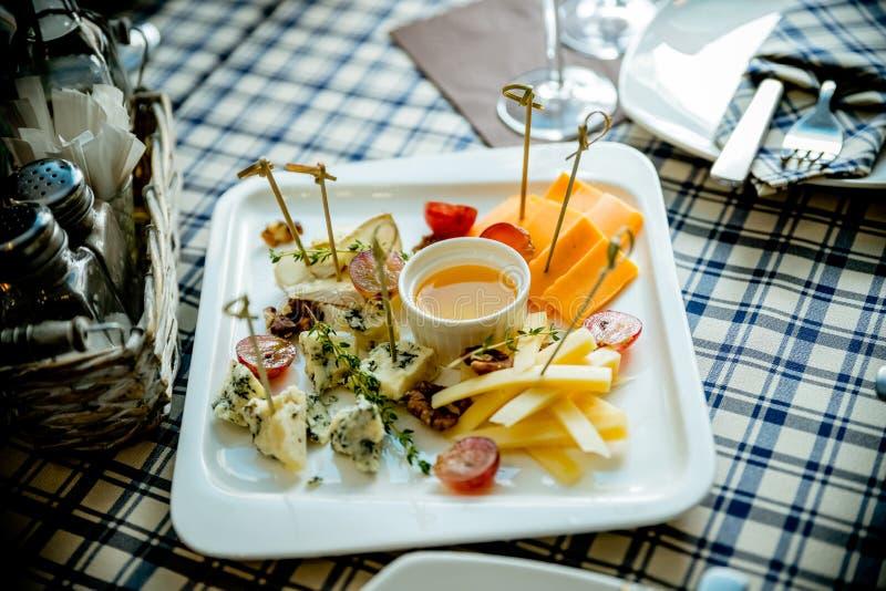Serowego talerza asortyment różnorodni typ ser i miód na bielu talerzu Sera i wina przyjęcia stół, perfect wakacje obrazy stock