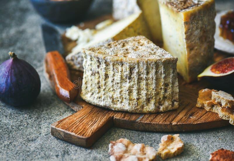 Serowy asortyment, figi, miód, chleb i dokrętki na pokładzie, obrazy stock