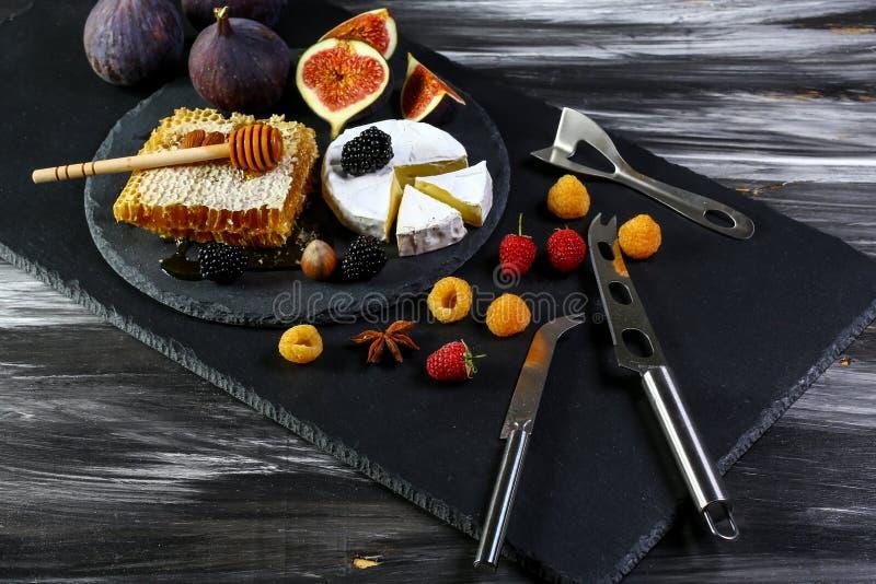 Serowy Camembert z nożem, owoc jagody na starym czarnym drewnianym stole i figi i Jedzenie dla wina i garmażerii romantycznej, se zdjęcia stock