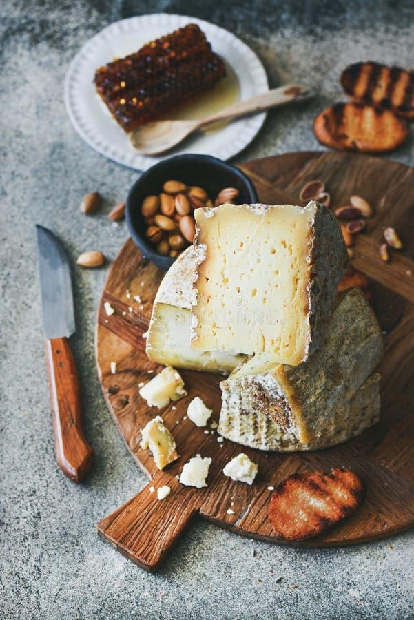 Serowy półmisek z serowym asortymentem, dokrętkami, miodem i chlebem, obrazy stock