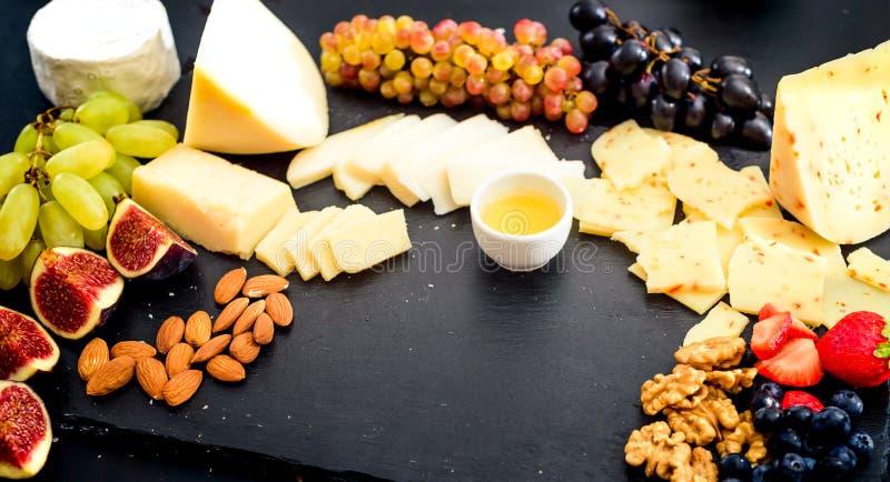 Serowy talerz Asortyment ser z orzechami włoskimi, migdałami, winogronami, figami, truskawkami, czarnymi jagodami i miodem na kam obraz stock