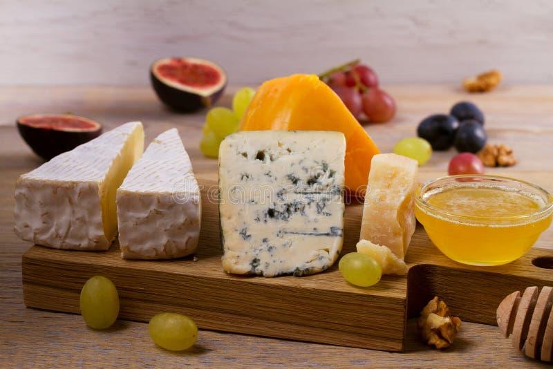 Serowy talerz Różnorodni typ ser z winogronami, miodem, figami i dokrętkami na nieociosanym drewnianym stole, obraz stock