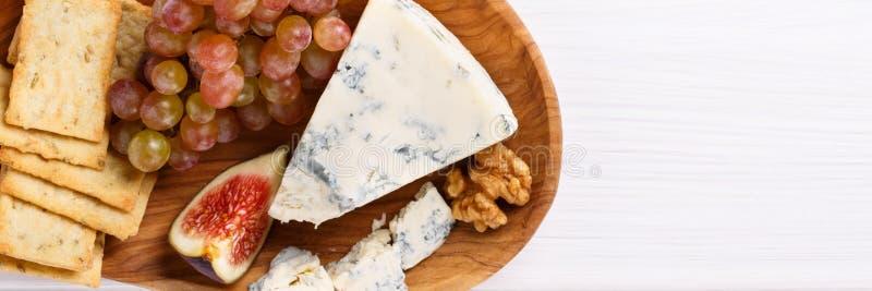Serowy talerz z błękitnym serem, winogronami, figami, krakersami i dokrętkami na bielu stole, fotografia royalty free