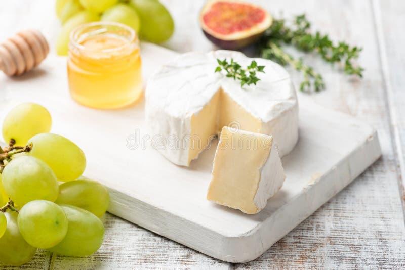 Serowy talerz z brie, camembert, miodem i owoc, obrazy stock