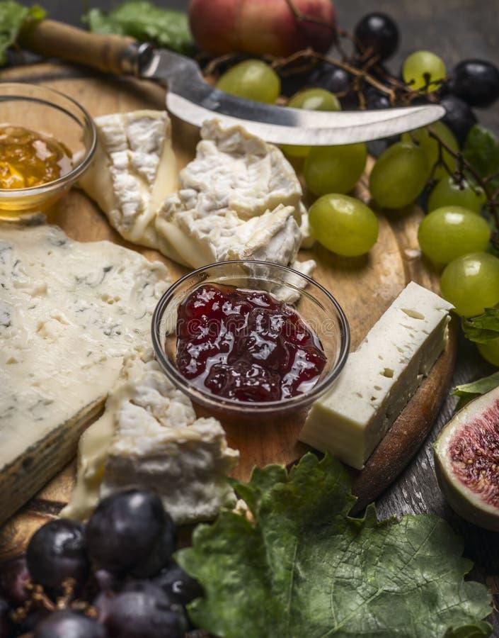 Serowy talerz z Gorgonzola, Camembert dżemem i miodem, winogrona, brzoskwinia na drewnianym tnącej deski zakończeniu up zdjęcia royalty free