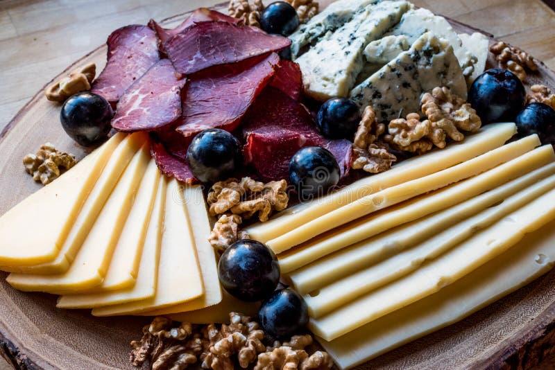 Serowy talerz z uwędzonym mięsem, orzechami włoskimi i winogronami na drewnianej powierzchni, obraz stock