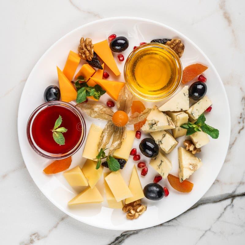 Serowy talerz, zielony ser, brie ser słuzyć z winem, chlebowymi kijami i miodem nad światło marmuru tłem, Przek?ski i wino obraz royalty free
