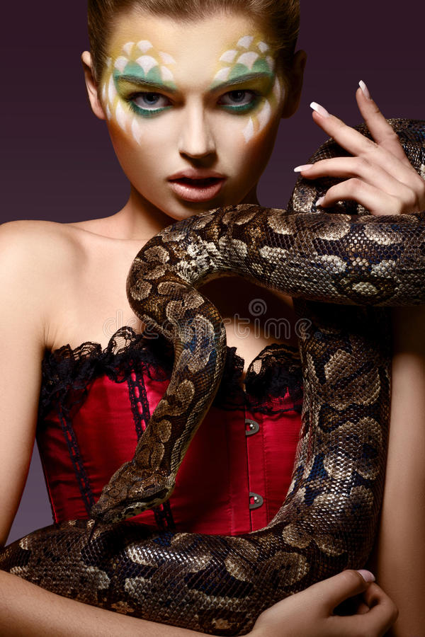 Serpent. Fantasy. Fancy Woman holding Tamed Snake in Hands royalty free stock photos