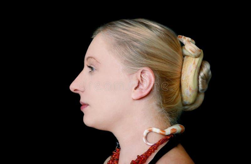 Serpent sur la tête de femme Boa constrictor albino, espèce non venimeuse de serpent, rampe les cheveux et enroule les cheveux de image stock
