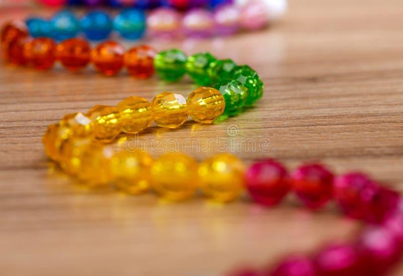 Serpente de grânulos coloridos em um fundo de madeira imagens de stock