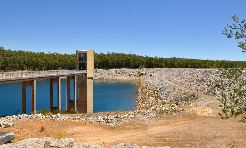 Serpentine Dam. View of elevated bridge with sand and rock bordering the Serpentine Dam with green trees under a blue sky in Serpentine, Western Australia stock images
