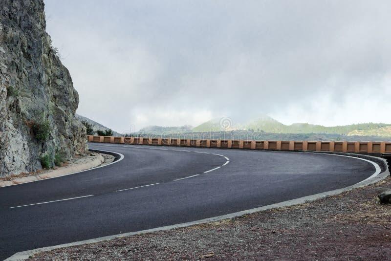Serpentine Mountain Roads i låga Gray Clouds, gröna kullar och nya Asphalt Road Kopiera utrymme f?r text f?r dublin f?r bilstadsb royaltyfria foton