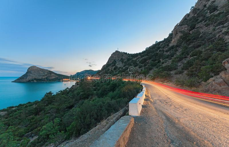 The serpentine in the mountains with the light trace from a passing car. In twilight on a background of mountains, headland and sea beyond stock image