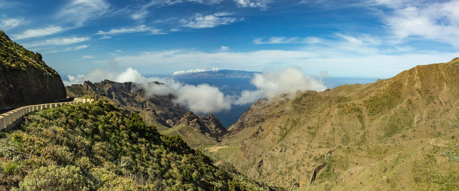 Serpentine road and amazing view of Blue sky with beautiful fluffy clouds, Island of La Gomera, mountain landscape. Sunny day on royalty free stock photos