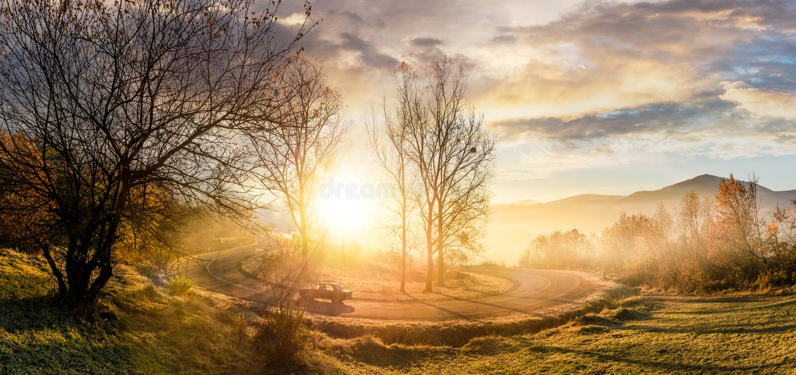 Serpentine turnaround on foggy sunrise. Naked trees on grassy hillsides under gorgeous cloudy sky over the mountain ridge in a distance. beautiful late autumn stock photography