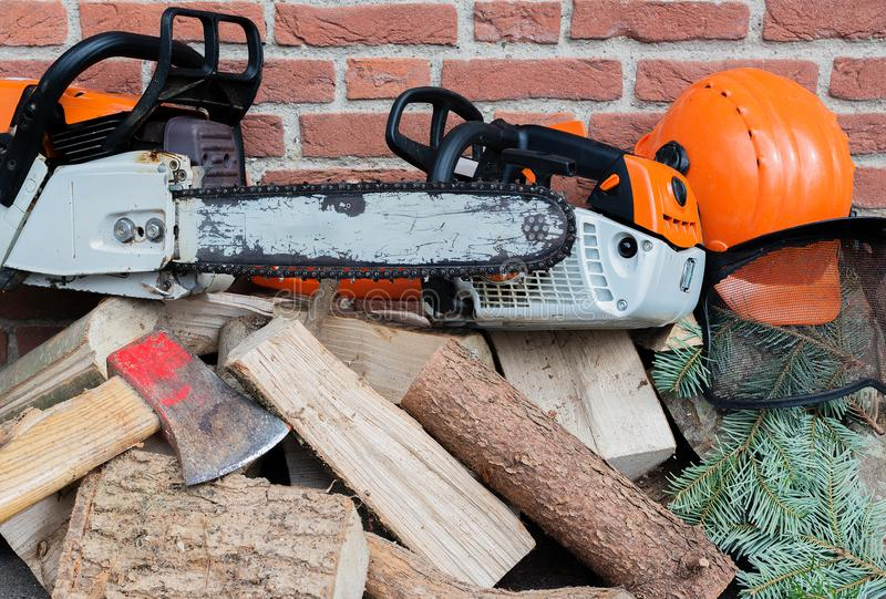 Serra de cadeia conduzida gasolina em uma pilha de madeira fotos de stock