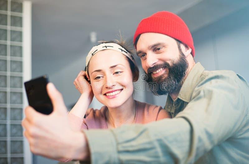 Serrage des moments heureux Beaux jeunes couples affectueux collant entre eux et faisant le selfie tout en se reposant sur photo libre de droits
